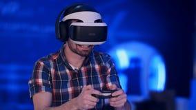 Hombre feliz del videojugador que juega a los videojuegos con las auriculares y la palanca de mando de la realidad virtual Imagenes de archivo