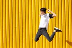 Hombre feliz, divertido del estudiante que salta con los auriculares en un fondo amarillo de la pared Concepto adolescente de la  Imagen de archivo libre de regalías