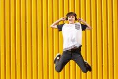 Hombre feliz, divertido del estudiante que salta con los auriculares en un fondo amarillo de la pared Concepto adolescente de la  Foto de archivo libre de regalías