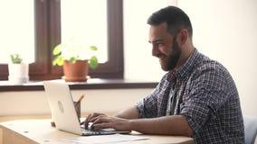 Hombre feliz emocionado sobre la pantalla de mirada en línea de la PC del triunfo en almacen de video