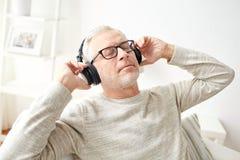 Hombre feliz en auriculares que escucha la música en casa imagen de archivo