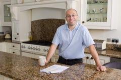 Hombre feliz en cocina moderna imagen de archivo