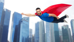 Hombre feliz en el cabo rojo del super héroe que vuela sobre ciudad Foto de archivo libre de regalías