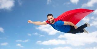 Hombre feliz en el cabo rojo del super héroe que vuela sobre el cielo Fotografía de archivo libre de regalías