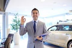 Hombre feliz en el salón del salón del automóvil o del coche Imagen de archivo libre de regalías