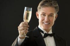 Hombre feliz en el smoking que detiene a Champagne Flute Foto de archivo