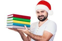 Hombre feliz en el sombrero de Papá Noel con un libro en el fondo blanco Fotos de archivo