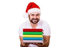 Hombre feliz en el sombrero de Papá Noel con un libro en el fondo blanco Imagen de archivo