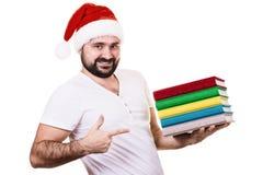 Hombre feliz en el sombrero de Papá Noel con un libro en el fondo blanco Foto de archivo libre de regalías