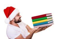 Hombre feliz en el sombrero de Papá Noel con un libro en el fondo blanco Imágenes de archivo libres de regalías
