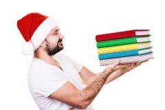 Hombre feliz en el sombrero de Papá Noel con un libro en el fondo blanco Fotografía de archivo libre de regalías