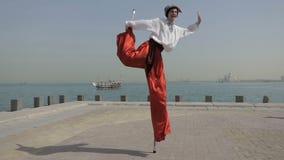 Hombre feliz en el traje cosaco que salta en un zanco en un muelle del mar en Dubai en el slo-MES metrajes