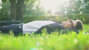 Hombre feliz en el traje que miente en hierba y que disfruta del día soleado, armonía con la naturaleza almacen de video