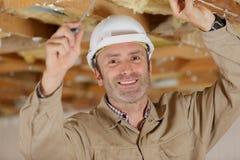 Hombre feliz en el uniforme del constructor que instala el techo suspendido fotografía de archivo