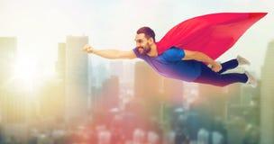 Hombre feliz en el vuelo rojo del cabo del super héroe en el aire Foto de archivo