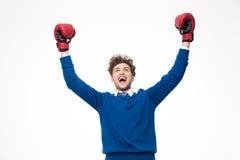 Hombre feliz en guantes de boxeo que celebra un triunfo Imagen de archivo libre de regalías