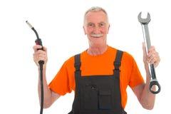 Hombre feliz en guardapolvo anaranjado y gris con la llave Foto de archivo libre de regalías