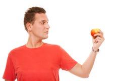 Hombre feliz en la camisa roja que sostiene la manzana. Nutrición sana de la atención sanitaria de la dieta. Fotos de archivo libres de regalías
