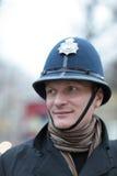 Hombre feliz en sombrero británico de la policía Imagen de archivo libre de regalías