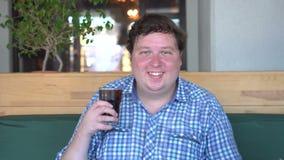 Hombre feliz gordo que sostiene un vidrio de cola del refresco y que ríe, sentándose en café bebida almacen de video