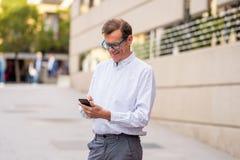 Hombre feliz hermoso en su 60s que envía y que recibe mensajes de texto en su teléfono móvil en viejo hombre usando la red social fotografía de archivo