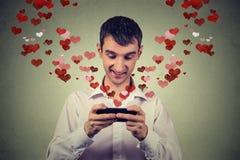 Hombre feliz hermoso que envía recibiendo el mensaje de texto del SMS del amor en el teléfono móvil Imagenes de archivo