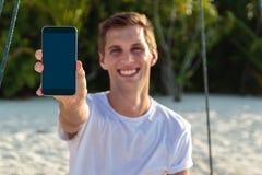 Hombre feliz joven asentado en un oscilaci?n que muestra una pantalla vertical del tel?fono Arena y selva blancas como fondo foto de archivo libre de regalías