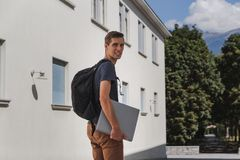 Hombre feliz joven con la mochila que camina a la escuela después de vacaciones de verano fotos de archivo