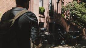 Hombre feliz joven con la mochila que camina a lo largo de la calle soleada de Brooklyn del verano en Nueva York usando la oficin almacen de metraje de vídeo