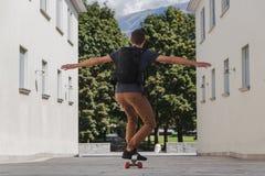 Hombre feliz joven con la mochila usando el longboard para que el ir enseñe después de vacaciones de verano foto de archivo