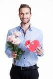 Hombre feliz joven con rosas rosadas y un regalo. Fotografía de archivo