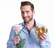 Hombre feliz joven con una rosa y un regalo. Fotografía de archivo libre de regalías