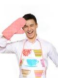 Hombre feliz joven del cocinero en la sonrisa del delantal fotos de archivo