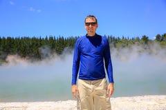 Hombre feliz joven en camisa azul Área termal de Wai-O-Tapu, NZ Fotos de archivo