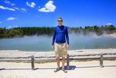 Hombre feliz joven en camisa azul Área termal de Wai-O-Tapu, NZ Foto de archivo