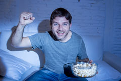 Hombre feliz joven en casa que mira el partido de deporte en la TV que anima el suyo para combinar gesticulando el puño de la vic Imagen de archivo libre de regalías