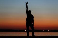 Hombre feliz joven en la puesta del sol Foto de archivo