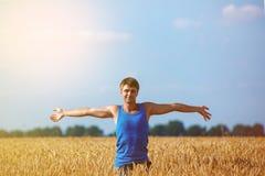 Hombre feliz joven en un campo de trigo Fotos de archivo libres de regalías