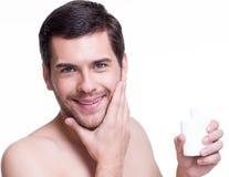 Hombre feliz joven que aplica la crema. Imagenes de archivo