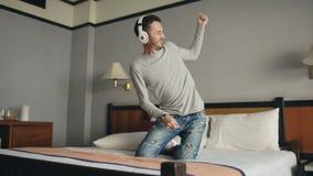 Hombre feliz joven que escucha la música con los auriculares inalámbricos y que baila en cama en la habitación almacen de video