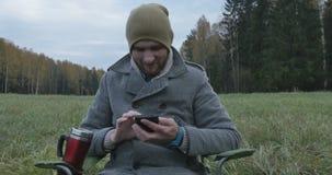 Hombre feliz joven que habla en el teléfono móvil en el parque almacen de metraje de vídeo
