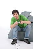 Hombre feliz joven que juega al juego video Foto de archivo libre de regalías