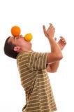 Hombre feliz joven que juega con el limón y la naranja Foto de archivo