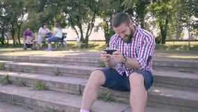 Hombre feliz joven que juega a juegos en smartphone en parque almacen de video