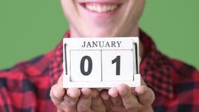 Hombre feliz joven que muestra el bloque de calendario contra fondo verde almacen de metraje de vídeo