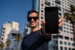 Hombre feliz joven que muestra una pantalla vertical del tel?fono horizonte de la ciudad como fondo imágenes de archivo libres de regalías