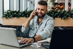 Hombre feliz joven que se sienta en oficina en la tabla, trabajando en el ordenador, hablando en el teléfono El Freelancer tiene  imagen de archivo