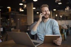 Hombre feliz joven que tiene llamada de teléfono en café fotografía de archivo