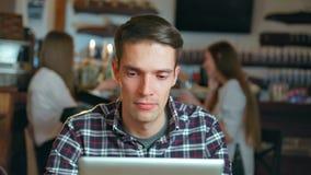 Hombre feliz joven que usa la tableta en un café metrajes
