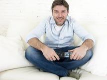 Hombre feliz joven que ve la TV el sentar en casa del sofá de la sala de estar que parece relajado gozando de la televisión Imagenes de archivo